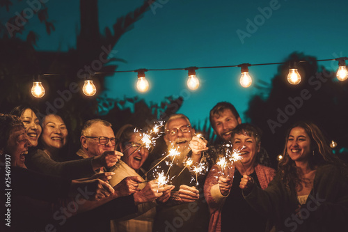 Fotografía Happy family celebrating with sparkler at night party outdoor - Group of people