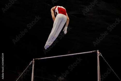 Spoed Fotobehang Gymnastiek male gymnast exercise on horizontal bar in black background