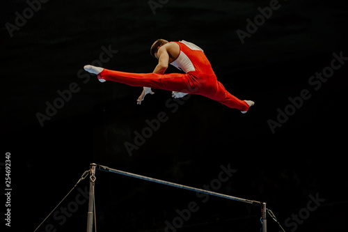 Spoed Fotobehang Gymnastiek exercise horizontal bar athlete gymnast on black background