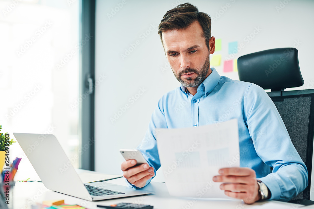 Fototapeta A man sitting at the desk at the office, checking financial documents and holding smartphone