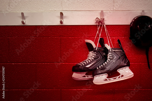 Hockey skates and helmet hanging in locker room with red gradient background and Wallpaper Mural
