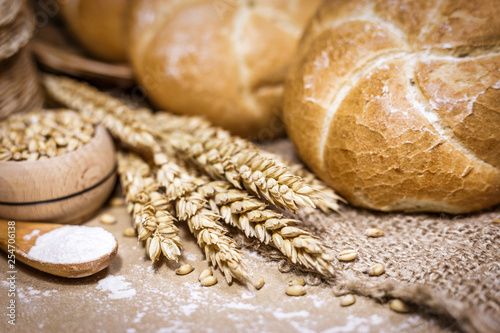 Fotografie, Obraz  Freshly baked bread, wheat and flour on a rustic background