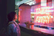 Young Woman Looking Through The Glass Next To A Club With A Window With Neon Lights Take Away