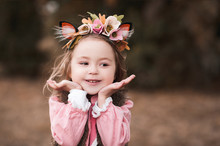 Cute Smiling Kid Girl 3-4 Year Old Wearing Floral Hairband Outdoors. Spring Season.