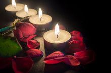 Four Tea Candles And Rose Petals In The Dark