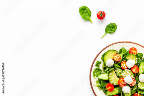 Fotografia Fresh salad with mozzarella, spinach, cherry tomatoes, cucumber on plate on whit