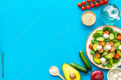 Cooking fresh salad. Vegetables, greens, spices, plate of salad on blue kitchen desk top view space for text