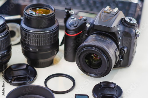 Obraz image of outdoor photographic equipment on a white table with natural light with assorted lenses - fototapety do salonu