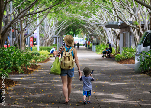 Photo Mother and child walking down tree-lined path in the tropics
