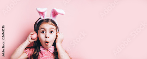 Fotografía Cute little girl with bunny ears on pink background.