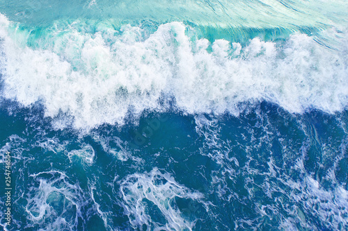 Deurstickers Water wave with white foam in the bright blue surface of the sea
