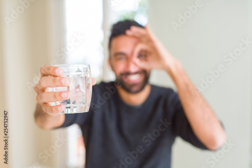 Tableau sur Toile Handsome hispanic man drinking a fresh glass of water with happy face smiling do