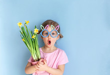 Cute Little Child Wearing Bunny Ears Glasses And Holding Flowers On Easter Day. Easter Girl Portrait, Funny Emotions, Surprise. Copyspace For Text