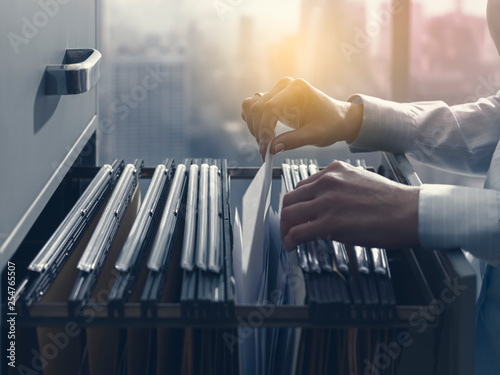 Fotografie, Obraz Office clerk searching files in the filing cabinet