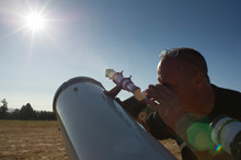 Astronomer Looking Bright Sun Through Telescope Against Clear Sky During Sunny Day