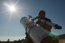 Low Angle View Of Astronomer Looking Bright Sun Through Telescope Against Clear Sky During Sunny Day