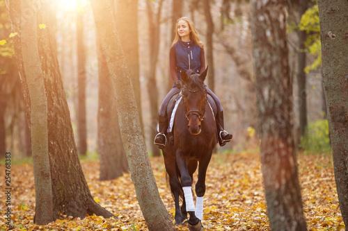 Fotografía  Teenage girl riding horse in autumn park
