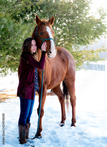 brunette teenage girl with her sorrel horse. She is holding him with lead rope, he is wearing blue halter. green trees background