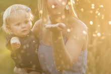 Mother And Daughter Blowing Glitter