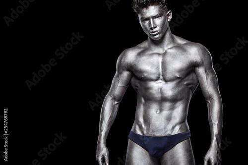 Fotografía  Brutal strong muscular bodybuilder athletic man pumping up muscles on black background