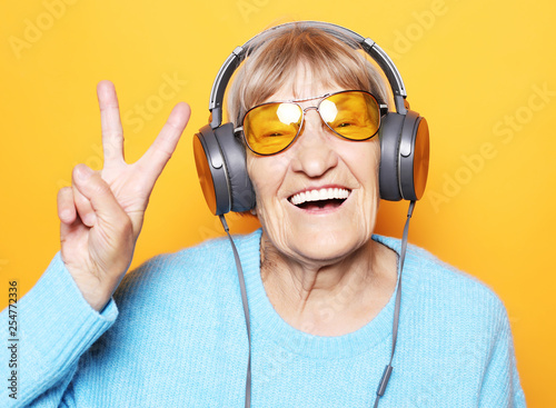 Fotografía  Funny old lady listening music and showing thumbs up.