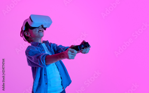 canvas print motiv - kegfire : Expressive boy playing VR game in glasses