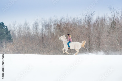 Photo blonde young woman riding her horse through snow bareback on a winter day