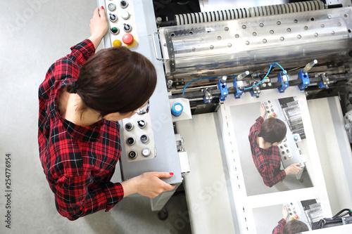 Drukarnia. Kobieta pracuje przy maszynie foliującej.