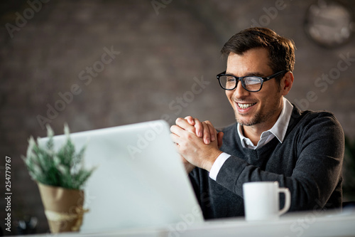 Fotografie, Obraz  Happy male entrepreneur using laptop while working in the office.