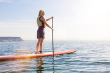 Happy, Healthy Woman Wearing A Life Jacket Paddleboarding. Women's Outdoor Adventure Summer Water Sports.