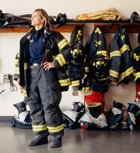 Thoughtful Female Firefighter Standing In Fire Station