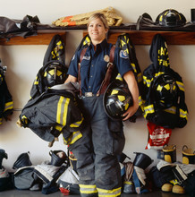 Portrait Of Female Firefighter With Helmet Standing In Fire Station