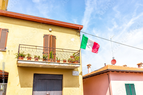 Fotografie, Obraz  Chiusi, Italy street with Italian flag on building exterior hanging on balcony o