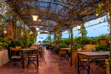 Typical Italian Rooftop Restaurant Wooden Tables In Tuscany With Covered Roof Pergola Vine Canopy With Empty Seats, Chairs And Nobody In Rustic Romantic Architecture