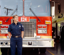 Smiling Female Woman Firefighter In Uniform With Fire Engine Truck At Station. Happy, Confident, Successful Public Service Career Professional.