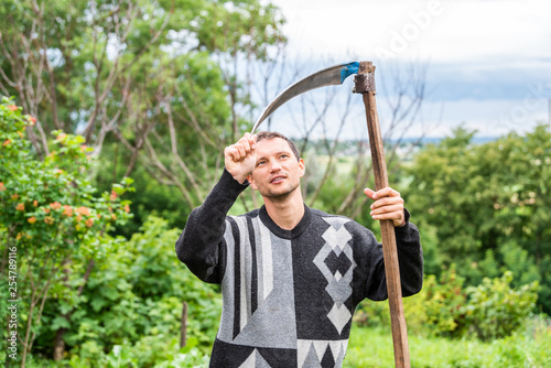 Happy young man farmer in garden standing with sickle scythe