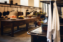Antique XIX Century Old Kitchen With Tools, Pans, Pots And Food Ingredients All Over Che Benches And Tables