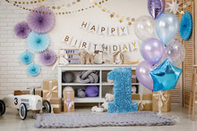 Birthday Blue And Purple Decorations With Gifts, Toys, Garlands And Figure For Little Baby Party On A White Bricks Background.