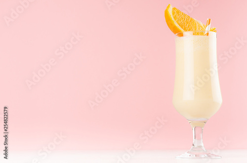 Bright oranges milkshake in elegance glass with slices orange on white wooden table and pastel light pink wall.