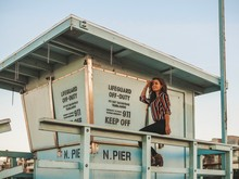 Brunette Girl In Striped Bright Shirt With Long Hair Sits On Lifeguard Tower Near Manhattan Beach Pier In Los Angeles At Sunrise