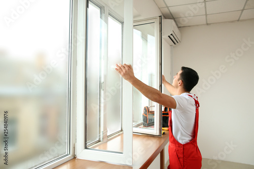 Young worker checking window after repair