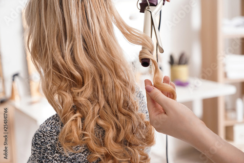 Fotografie, Obraz  Hairdresser curling long hair of young woman in salon