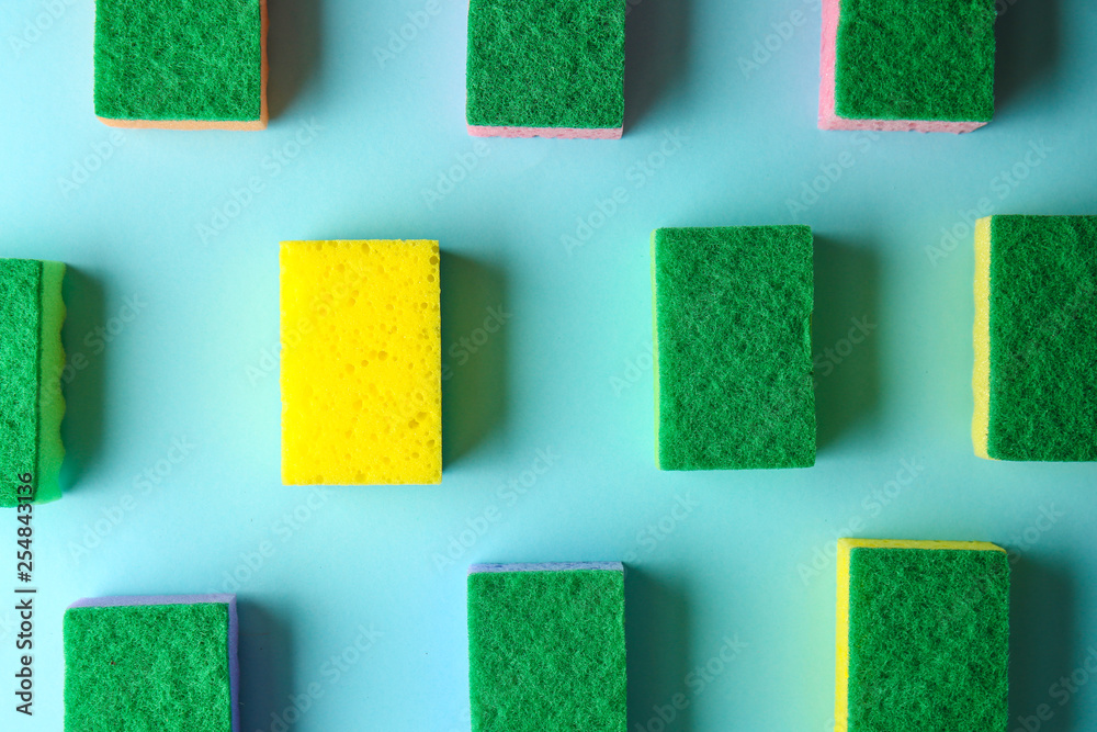 Fototapeta Yellow sponge among green ones on color background. Concept of uniqueness