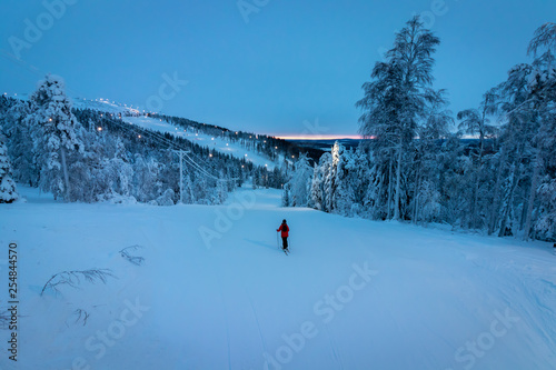 Solo skier on lit piste lined with snow covered pine trees in Levi, Lapland, Fin Tableau sur Toile