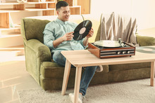 Young Man Listening To Music On Record Player At Home