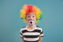 Cute Little Boy With Clown Makeup On Color Background. April Fools' Day Celebration