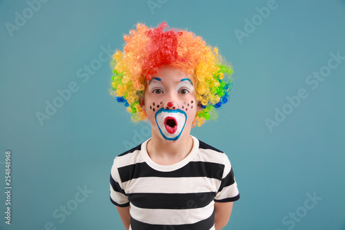 Leinwand Poster Cute little boy with clown makeup on color background