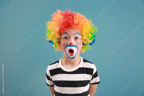Fotografiet Cute little boy with clown makeup on color background
