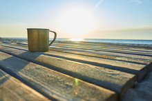 A Metal Mug On Wooden Planks On The Shore Of The Sea In The East Sun