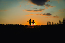 Silhouette Of Happy Boy And Gi...